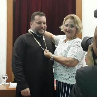 A mãe de Pe. João, D. Rita de Cassia Pires Barbosa Pecegueiro Anchieta, coloca o colar-insígnia do Instituto.